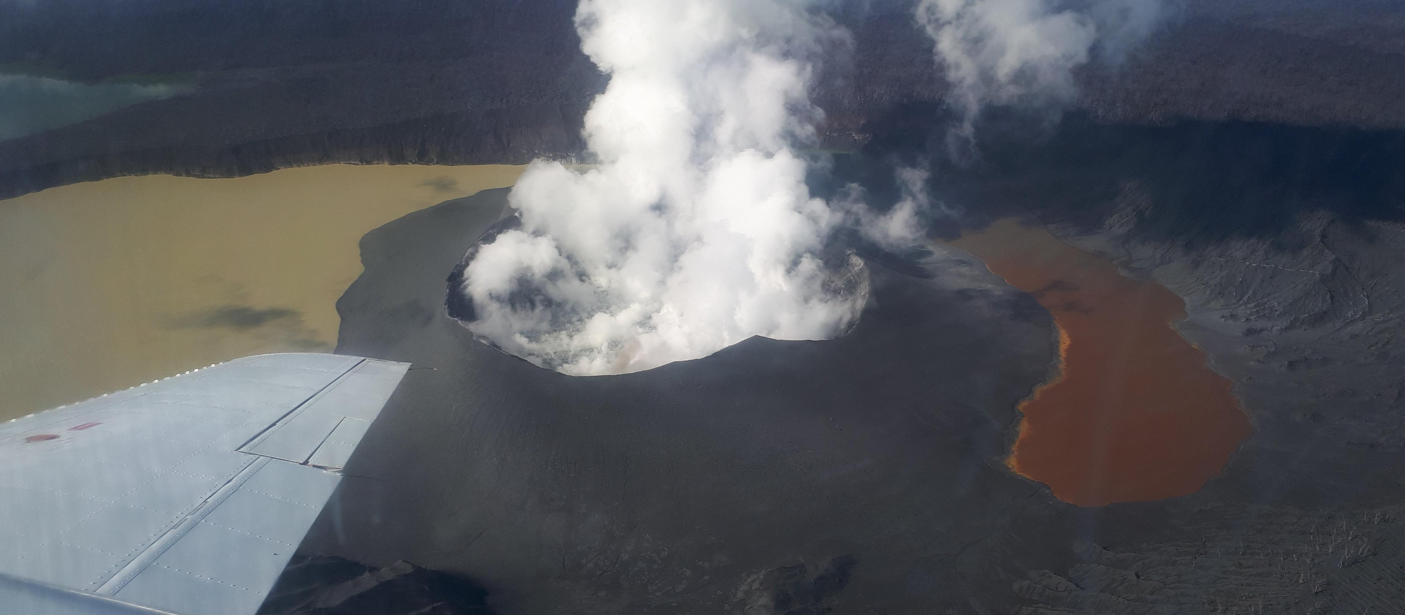 Ambae volcano and Lake Voui on 21 April 2018, Ambae Island, Vanuatu. The lake has been split into two due to the growth of the new volcanic cone. The visible landscape is covered with thick ash deposits. The dead trees in the lower right were killed over a decade ago during another eruptive episode. Photo credit: Natalia Deligne.