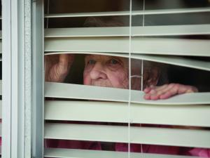Elderly woman looks through blinds
